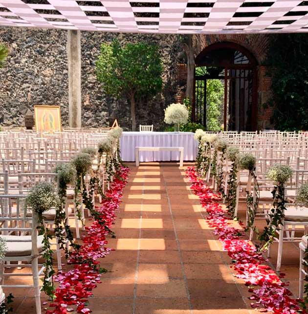Montaje para ceremonia nupcial con camino cubierta con pétalos de rosas Banquetes Escoffier CDMX
